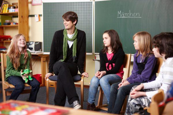 Lehrerin und Schüler bilden einen Stuhlkreis