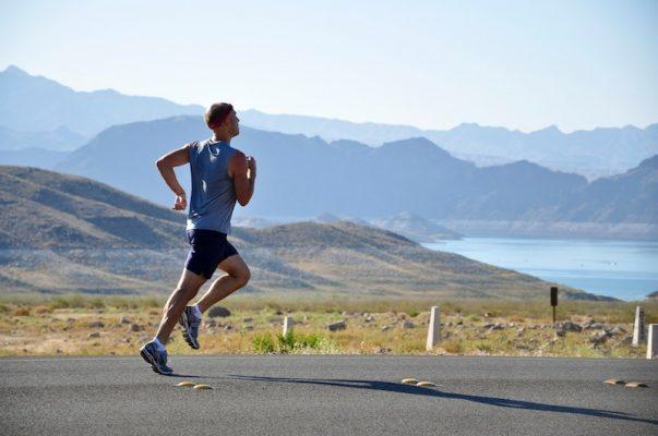 Ein Mann joggt auf der Straße, im Hintergrund sieht man einen See
