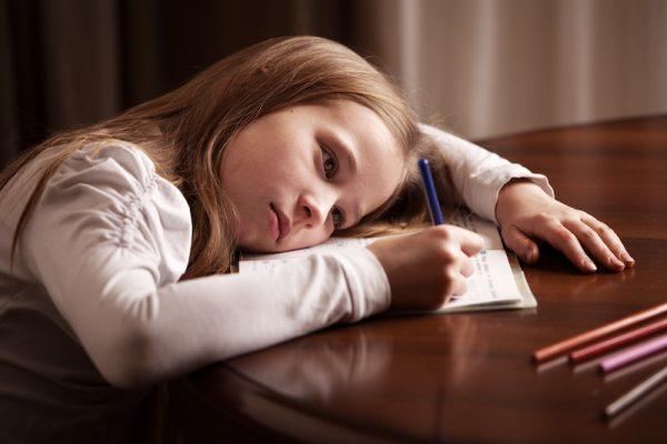 Mädchen schreibt lustlos in Heft